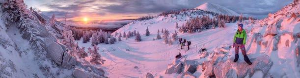 Eine Gruppe Wanderer, die Sonnenaufgang in den Winterbergen aufpassen Stockfotos
