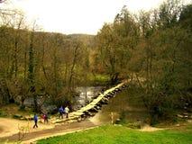 Eine Gruppe wandernde Touristen, kreuzen die alte Tarr-Schritt-Brücke lizenzfreie stockfotografie