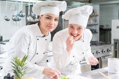Eine Gruppe weibliche junge Chefs, die Mahlzeit im Luxusrestaurant prepairing sind lizenzfreie stockbilder