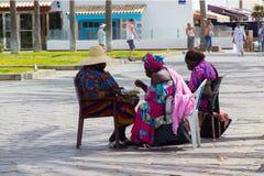 Eine Gruppe westafrikanische Schwestern genießen einen gut erworbenen Snack als das Nehmen ein Rest von ihrem flechtenden Geschäf stockbild
