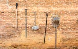 Eine gute Idee, Gartenwerkzeuge auf brauner Wand zu halten L Stockfotografie