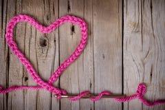 Eine Häkelarbeitkette in Form eines Herzens Stockbilder