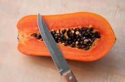 Eine Hälfte der Papaya schnitt durch scharfes Messer auf hölzerner Wand Stockfotos