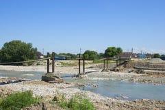Eine Hängebrücke über einem Gebirgsstrom Lizenzfreies Stockfoto