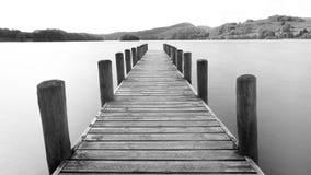 Eine hölzerne Anlegestelle, die heraus über einen See ausdehnt stockbilder