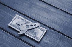 Eine hölzerne Figürchen einer Rakete auf einem Satz Dollar, auf einem blauen Ba Stockfotos