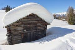Eine hölzerne Kabinenhütte im Winterschneehintergrund Stockbild
