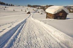 Eine hölzerne Kabinenhütte im Winterschneehintergrund Lizenzfreies Stockbild