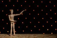 Eine hölzerne Marionettenpuppe steht auf einer Tabelle und zeigt Hände oben auf einem b Stockfotografie