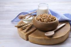 Eine hölzerne Schüssel der Hintermischung mit Mandeln, Rosinen, Samen, Acajoubaum, Haselnussnüssen, Glas Milch und Honig auf weiß Lizenzfreie Stockfotos