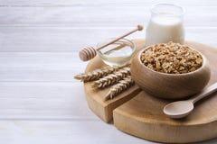 Eine hölzerne Schüssel der Hintermischung mit Mandeln, Rosinen, Samen, Acajoubaum, Haselnussnüssen, Glas Milch und Honig auf weiß Lizenzfreies Stockbild