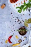 Eine hölzerne Schüssel für die Würze nahe bei einem Teller auf einem grauen Hintergrund Gewürze mit heißen bunten Pfeffern, Lorbe Stockfotografie