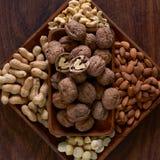 Eine hölzerne Schüssel voll Walnüsse, Erdnüsse, Mandeln, Acajoubäume und Macadamia auf einem hölzernen Brett stockbilder