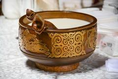 Eine hölzerne Schale mit dem Schöpflöffel eines Nomaden Milch wird in die Schale gegossen Kulturerbe der kasachischen Leute stockfoto