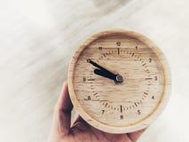 Eine hölzerne Uhr in der Hand, die Zeit hat kein Rückholkonzept stockfotografie