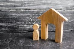 Eine hölzerne Zahl eines Mannes steht nahe einem Holzhaus auf einem grauen konkreten Hintergrund Konzept von Immobilien, mietend  lizenzfreie stockfotos