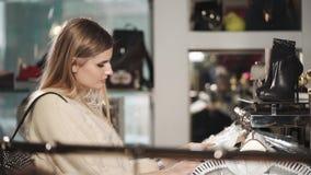 Eine hübsche Dame beschließt Kleidung, um im Einkaufszentrum zu kaufen, um ihre Garderobe zu aktualisieren stock video