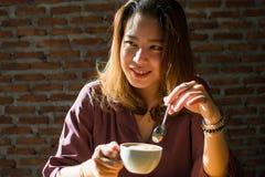 Eine hübsche Frau betrachtet jemand beim Trinken des Kaffees lizenzfreies stockfoto
