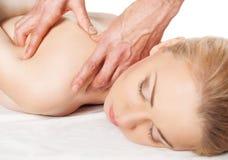 Eine hübsche Frau, die eine Schulter und eine rückseitige Massage erhält stockfotos