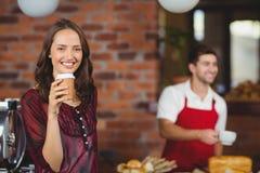 Eine hübsche Frau, die einen Kaffee trinkt lizenzfreie stockfotos