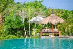 Eine hübsche Frau, die im tropischen Schatten ein Pool sitzt Stockfotografie