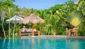 Eine hübsche Frau, die im tropischen Schatten ein Pool 2 sitzt Lizenzfreie Stockfotografie