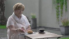 Eine hübsche Greisin isst ein Hörnchen und einen trinkenden Tee Sie sitzt in der Terrasse stock video footage
