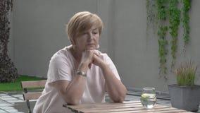 Eine hübsche Greisin sitzt in der Terrasse draußen Sie ist besorgt stock video
