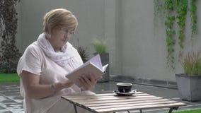 Eine hübsche Greisin sitzt draußen in der Terrasse und liest ein Buch stock footage