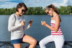 Eine hübsche Jugendliche und ihre schöne Mutter benutzen Smartphones, Stockfotografie