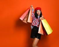 Eine hübsche junge Frau stilvoll gekleidet in einem Hut mit Taschen nach dem Einkauf lizenzfreies stockfoto