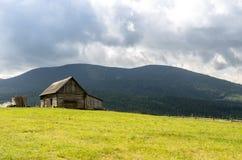 Eine Hütte in den Bergen Hölzernes Haus in den Bergen Das Haus wird vom Blockhaus gemacht Lizenzfreie Stockfotos