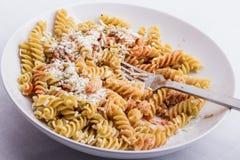 Eine halb volle weiße Platte, wenn das fusilli, mit Tomatensauce bedeckt ist Lizenzfreie Stockbilder