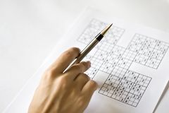 Eine Hand auf sudoku Rasterfeld lizenzfreies stockbild