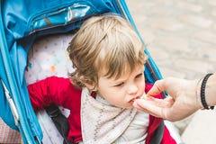 Eine Hand, die den Mund eines kleinen Mädchens abwischt Stockbilder
