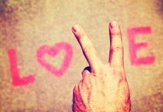 Eine Hand, die ein Friedenszeichen für den Buchstaben V in der Wortliebe macht Lizenzfreie Stockbilder
