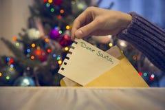 Eine Hand, die ein Papier mit lieber Sankt-Aufschrift in einen Umschlag auf einen Holztisch gegen verzierten Weihnachtsbaum setzt stockfoto