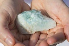 Eine Hand, die ein Stück Aquamarin hält Stockbild