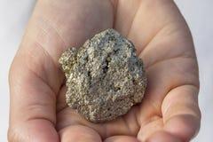 Eine Hand, die ein Stück Pyrit hält Stockfotos