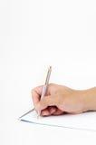 Eine Hand, die eine Feder anhält, um auf einen Notizblock zu schreiben lizenzfreies stockfoto
