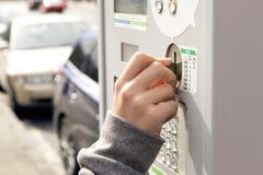 Eine Hand, die eine Münze in eine Parkuhr einfügt Lizenzfreie Stockbilder