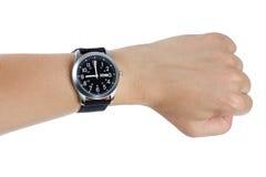 Eine Hand, die eine schwarze Armbanduhr trägt Lizenzfreie Stockfotografie