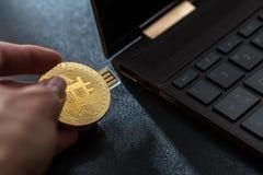 Eine Hand, die in einem Bitcoin-Daumen-Antrieb in Fensterlaptop verstopft Lizenzfreie Stockfotos