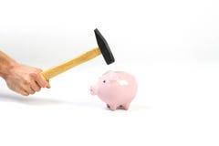 Eine Hand, die einen Hammer hält, der über ein stehendes rosa Sparschwein angehoben wird Lizenzfreie Stockbilder