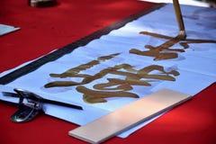 Eine Hand, die einen Malerpinsel hält, schreibt mit goldenem Tintenfrühlingsdistichon Übersetzung des Charakters ist neues Jahr stockfotografie