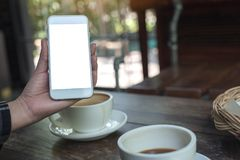 Eine Hand, die einen weißen Handy mit leerem Tischplattenschirm mit Kaffeetassen auf Holztisch im Café hält und zeigt Lizenzfreies Stockfoto
