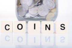 Eine Hand, die Glas Geld hält Lizenzfreie Stockfotos