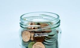 Eine Hand, die Glas Geld hält Stockbilder
