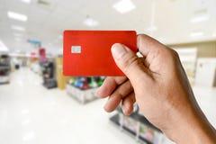 Eine Hand, die Kreditkarte auf unscharfem Elektronikladen hält Lizenzfreies Stockfoto