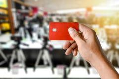 Eine Hand, die Kreditkarte auf unscharfem Kamerashopspeicher hält Lizenzfreie Stockbilder